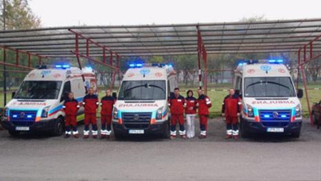 Zdjęcie przedstawia ratowników medycznych stojących obok nowo zakupionych ambulansów
