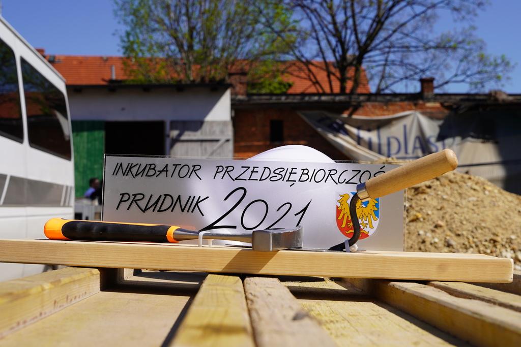 """Zdjęcie przedstawiające tabliczkę pamiątkową z napisem """"Inkubator przedsiębiorczości Prudnik 2021"""" położonej na stole wraz z młotkiem oraz kielnią"""