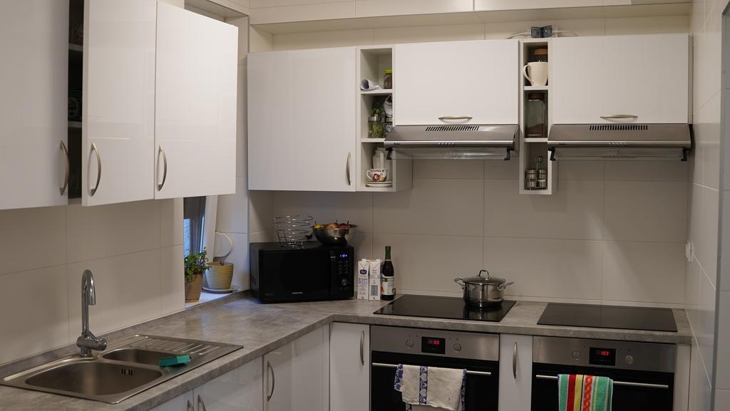 Kuchnia wraz z zabudową kuchenną, płytami indukcyjnymi, piekarnikami oraz zlewozmywakiem