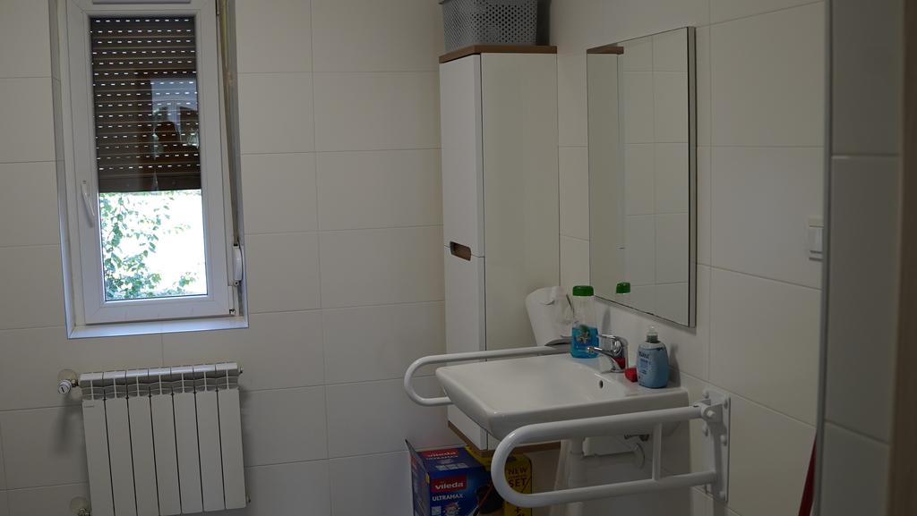 Toaleta z uchwytami dla niepełnosprawnych przy armaturze